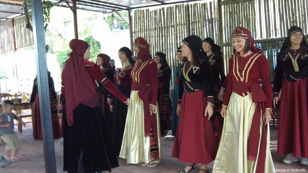 Туристы танцуют в грузинских костюмах